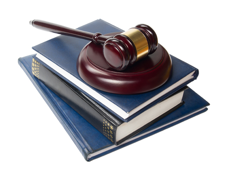prosecutor: Law concept - Law book with a wooden judges gavel on table in a courtroom or law enforcement office isolated on white background. Copy space for text. Stock Photo