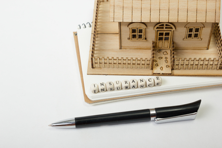 household insurance: Concept of housing purchase and insurance. Office desk table with supplies top view. Pen, notepad, model house, wooden block with word Insurance.