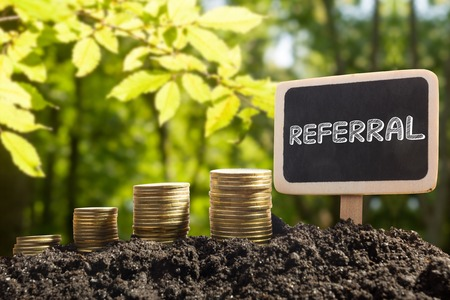referral: Referral - Financial opportunity concept. Golden coins in soil Chalkboard on blurred urban background.
