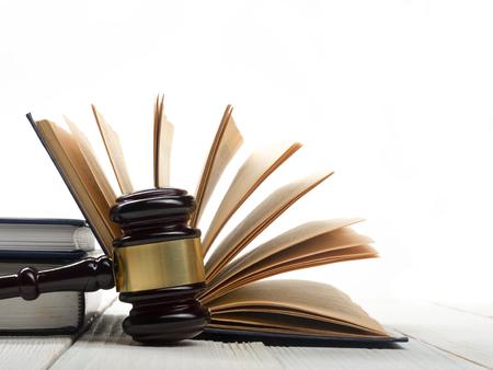 Law concept - Open wetsboek met een houten rechters hamer op tafel in een rechtszaal of wetshandhaving kantoor op een witte achtergrond. Kopieer ruimte voor tekst.