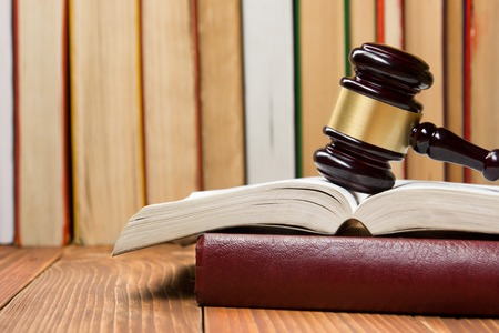 Law concept - Law book with a wooden judges gavel on table in a courtroom or law enforcement office Banque d'images
