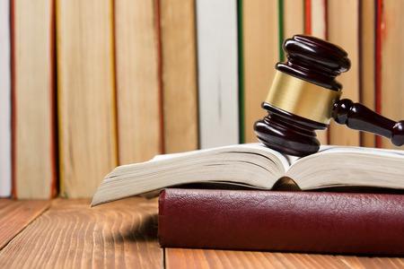 Law concept - Wet boek met een houten rechters hamer op tafel in een rechtszaal of wetshandhaving kantoor