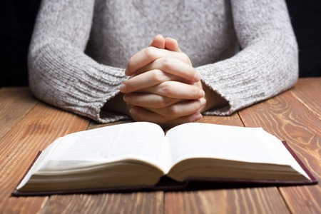catholic church: Woman hands praying with a bible in a dark over wooden table. Stock Photo