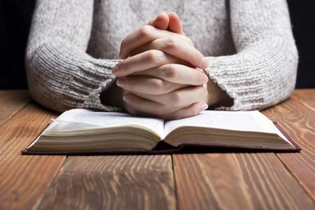 orando: Manos de la mujer que ruega con una biblia en una oscura sobre la mesa de madera.