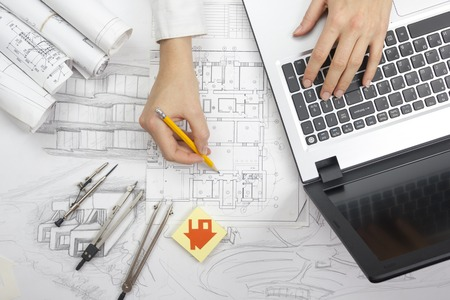 autocad: Architect working on blueprint. Architects workplace - architectural project, blueprints, ruler, calculator, laptop and divider compass. Construction concept. Engineering tools.
