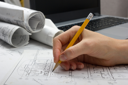 Architect working on blueprint. Architects workplace - architectural project, blueprints, ruler, calculator, laptop and divider compass. Construction concept. Engineering tools. Banco de Imagens