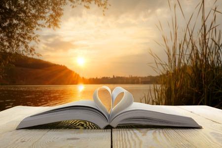自然な背景をぼかした写真の木製テーブルに開いた本。心の本のページ。学校に戻る領域をコピーします。