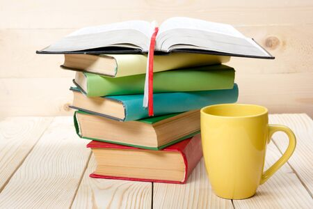 business book: Stack of colorful books, open book and cup on wooden table. Back to school. Copy space.