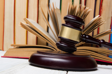 enforcement: Law concept - Law book with a wooden judges gavel on table in a courtroom or law enforcement office Stock Photo