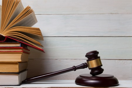Law concept - Law book with a wooden judges gavel on table in a courtroom or law enforcement office Stock Photo