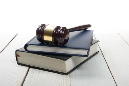 derecho penal: Concepto de la ley - la ley del libro abierto con un mazo de los jueces madera en la mesa en una oficina o sala aplicación de la ley aislado sobre fondo blanco. Copia espacio para el texto. Foto de archivo