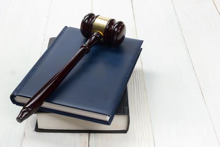 Law concept - Open wetsboek met een houten rechters hamer op tafel in een rechtszaal of wetshandhaving kantoor op een witte achtergrond. Kopieer ruimte voor tekst. Stockfoto