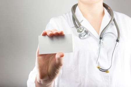 Female doctors hand holding blank business card. Close up shot on grey blurred background. Concept of Healthcare And Medicine. Copy space Stock Photo