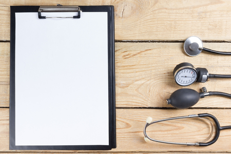 medical clipboard: Medical clipboard and stethoscope on wooden desk background. Top view. Workplace of a doctor