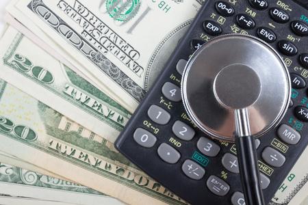 Financiële analyse, audit of accounting - stethoscoop over een rekenmachine en dollarbiljetten. Medische kosten, financiële concept.