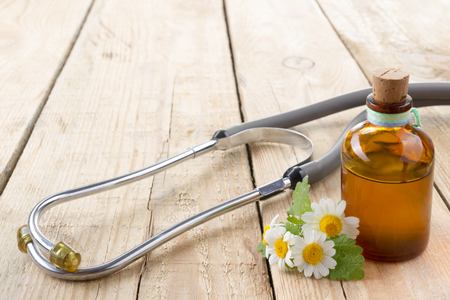 herb medicine: Fresh herb and medical stethoscope on wooden table. Alternative medicine concept
