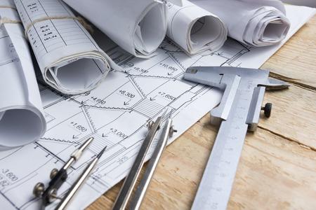 proyectos, planos, rollos Modelo arquitectónico y la brújula, pinzas divisor de madera en el fondo de la vendimia. Concepto de la construcción. herramientas de ingeniería. Espacio de la copia. Foto de archivo