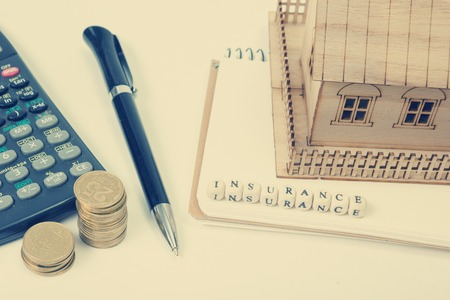 household insurance: Concept of housing purchase and insurance. Office desk table with supplies top view. Calculator. golden coins, pen, notepad, model house, wooden block with word Insurance.