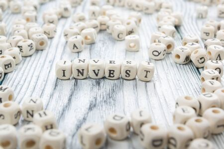 non stock: invest word written on wood block. wooden abc