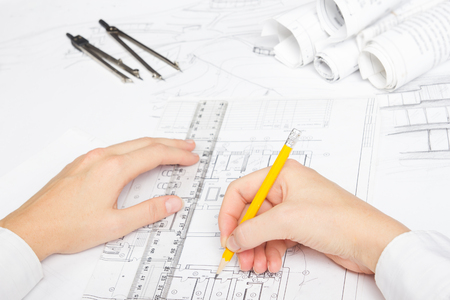 architect drawing: Architect working on blueprint. Architects workplace - architectural project, blueprints, ruler, calculator, laptop and divider compass. Construction concept. Engineering tools.