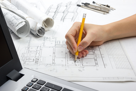 architect: Architect working on blueprint. Architects workplace - architectural project, blueprints, ruler, calculator, laptop and divider compass. Construction concept. Engineering tools.