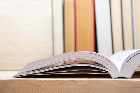 Offenes Buch, gebundene Bücher auf Holztisch. Zurück zur Schule. Kopieren Raum.