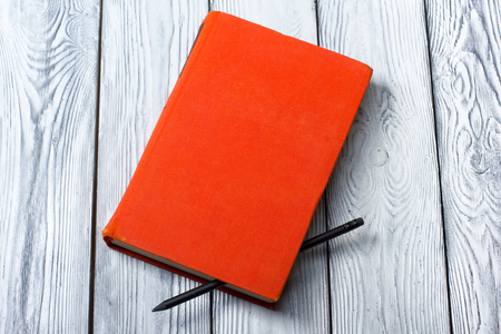 Blank red hardcover book with black pencil on white wooden background Stock Photo