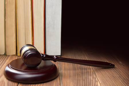 offense: Law concept - Law book with a wooden judges gavel on table in a courtroom or law enforcement office Stock Photo