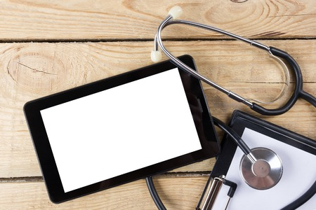 Workplace of a doctor. Tablet, stethoscope, clipboard on wooden desk background. Top view. Stock Photo