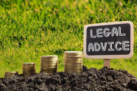 solicitors: Legal Advice - Financial opportunity concept. Golden coins in soil Chalkboard on blurred urban background. Stock Photo