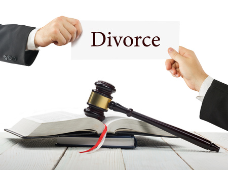 criminal case: Law book and wooden judges gavel on table in a courtroom or law enforcement office. Lawyer Hands holding business card with text Divorce.