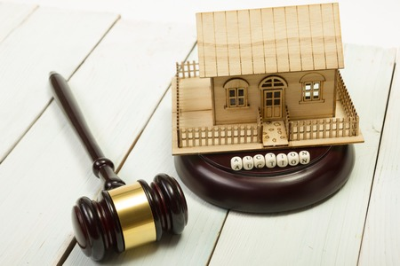 repossession: Auction. Law. Miniature House on wooden table and Court Gavel. Stock Photo
