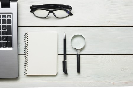 Office desk table with supplies. Top view. Copy space for text. Laptop, blank notepad, pen and magnifying glass. Stock Photo