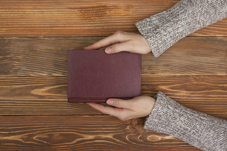 diary cover: A female hands hold a blank empty book or note, diary cover on the wood desk table, top view Stock Photo