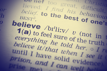transcription: Close-up of word in English dictionary. Belief, definition and transcription.