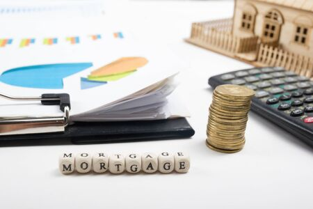 MORTGAGE word written on wood block, golden coins and clipbord with chart, model house.