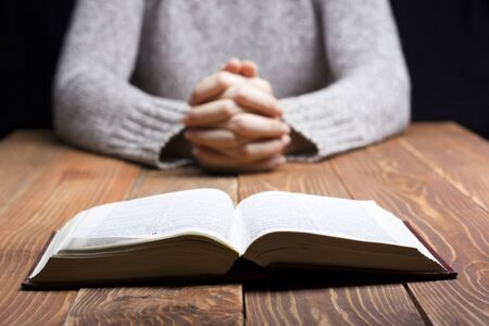 pray: Woman hands praying with a bible in a dark over wooden table. Stock Photo
