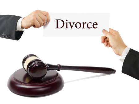 enforcement: Wooden judges gavel on table in a courtroom or law enforcement office. Lawyer Hands holding business card with text Divorce. Stock Photo