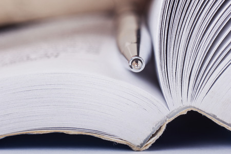 Close-up of open book and pen. Macro view