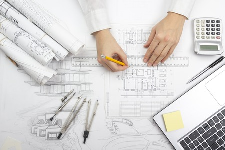 Architect working on blueprint. Architects workplace - architectural project, blueprints, ruler, calculator, laptop and divider compass. Construction concept. Engineering tools. Imagens - 52458663