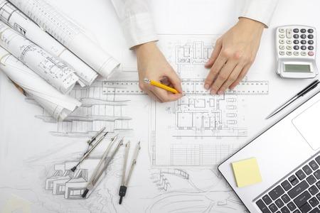Architekt pracuje nad planem. Architekci w miejscu pracy - projekt architektoniczny, plany, linijka, kalkulator, laptop i dzielnik kompasów. Budowa koncepcji. Narzędzia inżynierskie. Zdjęcie Seryjne
