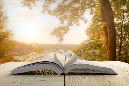 자연 백그라운드에 나무 테이블에 책을 엽니 다. 심장 책 페이지. 학교로 돌아가다. 공간을 복사하십시오.
