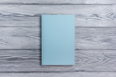 Blank book cover on textured wood background. Copy space,