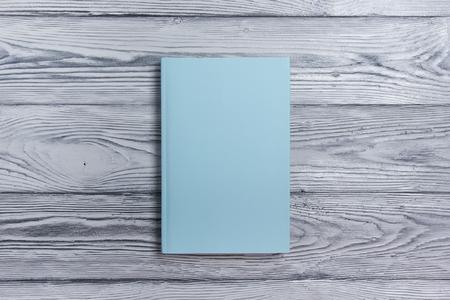 Blanco cover van het boek op een gestructureerde houten achtergrond. Exemplaar ruimte,