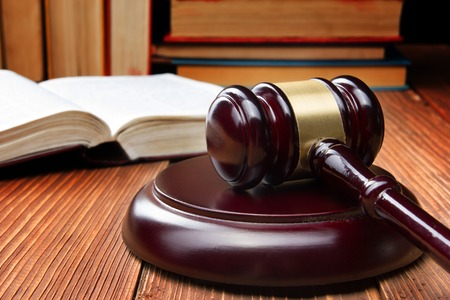 Law concept - Law book with a wooden judges gavel on table in a courtroom or law enforcement office 스톡 콘텐츠