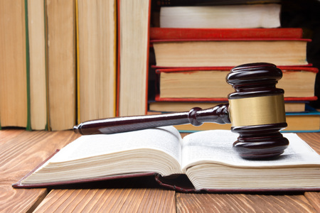 Law concept - Law book with a wooden judges gavel on table in a courtroom or law enforcement office Фото со стока