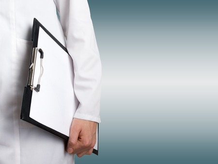 doctor s smock: Female doctors hand holding medical clipboard with blank sheet of paper and stethoscope on blue blurred background. Concept of Healthcare And Medicine. Copy space