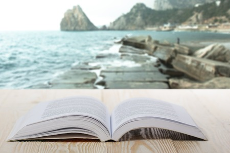 art book: Open book on wooden table on natural blurred background.