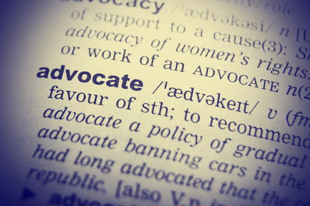 urging: Dictionary definition of advocate. Close up view with paper textures.
