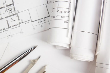architect tools: Workplace of architect - Architectural project, blueprints, rolls and  pen, divider compass on plans. Engineering tools view from the top. Construction background. Copy space for text